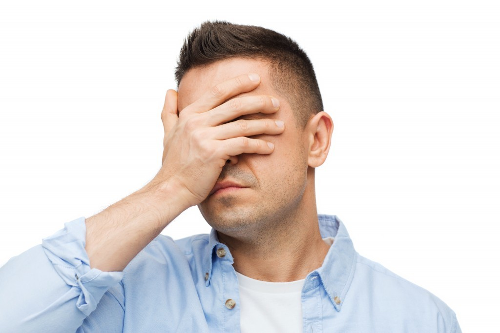 unhappy man covering his eyes by hand
