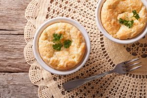 Two baked cheese souffle in white ramekens.